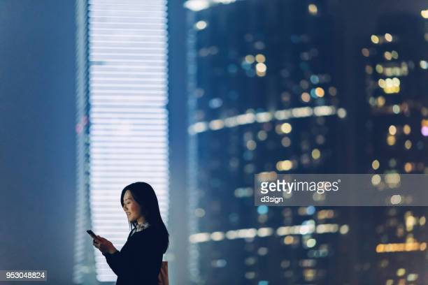 Young woman staying connected with the whole wide world with smartphone in city