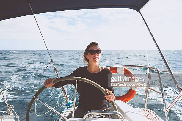 Young Woman Steering Boat On Sea