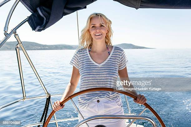 Young woman steering sailboat, Adriatic Sea