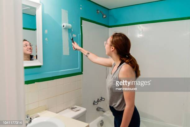 Young woman step by step DIY in home small bathroom.