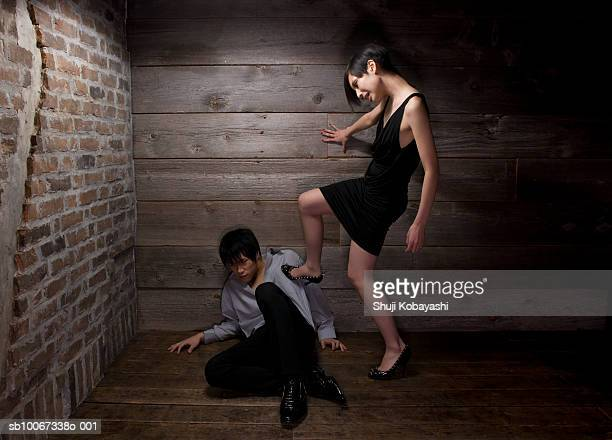 Young woman stepping on man