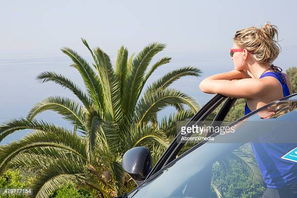 Young woman steps out of car in Tropical environment,.