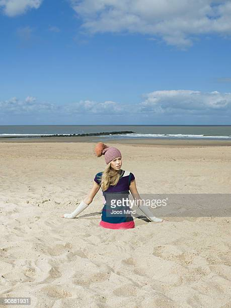 young woman sticking in the sand on beach
