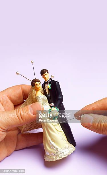 Young woman sticking pins in bride and groom figurines, close-up
