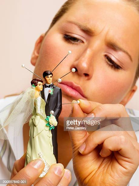 Young woman sticking pins in bride and groom figurines