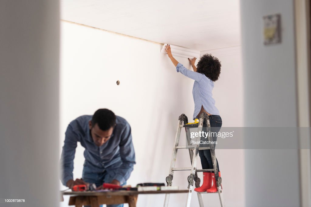 Young woman sticks cornice while young man works on plans on table home renovations : Stock Photo