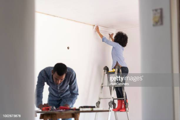 young woman sticks cornice while young man works on plans on table home renovations - architectural cornice stock photos and pictures