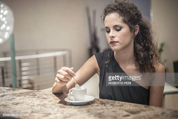 Young woman stirring coffee