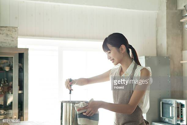 Young woman stirring cooking pot