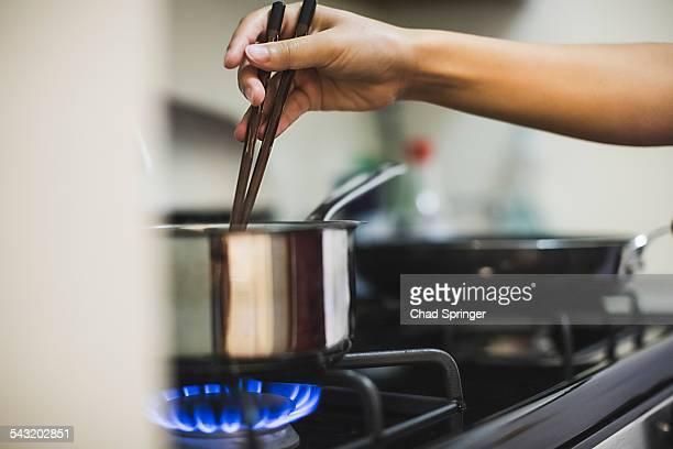 young woman stirring pan on cooker top with chopsticks - placa de fogão - fotografias e filmes do acervo