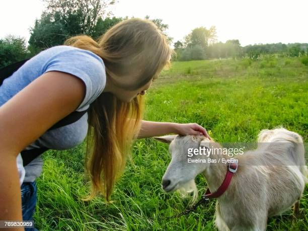 Young Woman Stoking Goat On Field