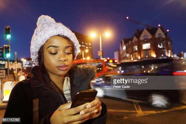 Young woman stood on city street at night with phone