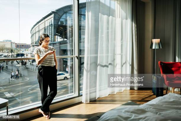 Young Woman Stood Using Phone In Modern Hotel Room
