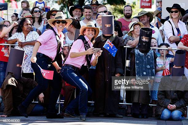 Young woman stop to take photos with participants dressed as Ned Kelly during the 43rd Tamworth Country Music Festival Calvalcade along Peel Street...