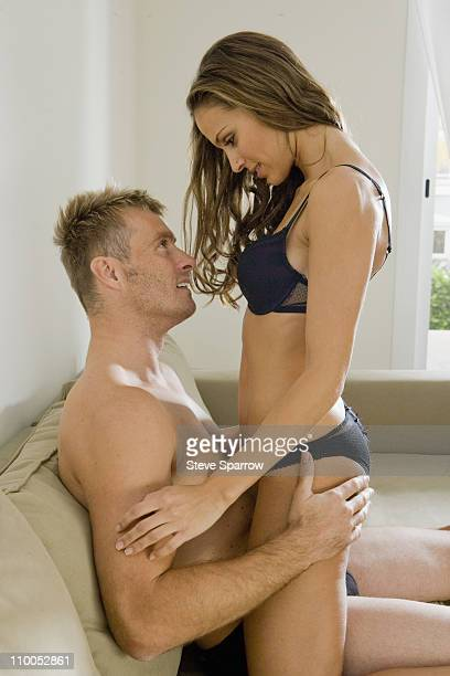 Young woman straddling young man on sofa