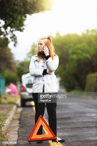 Junge Frau mit kaputten Autotelefone für Hilfe gestrandet