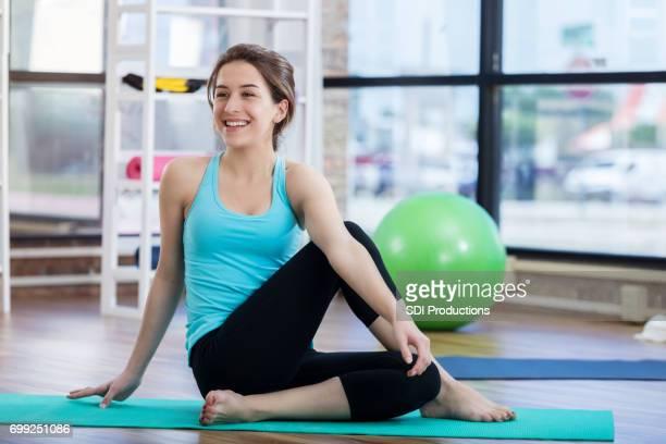 mujer joven extiende su cadera en la estera del ejercicio - cadera mujer fotografías e imágenes de stock