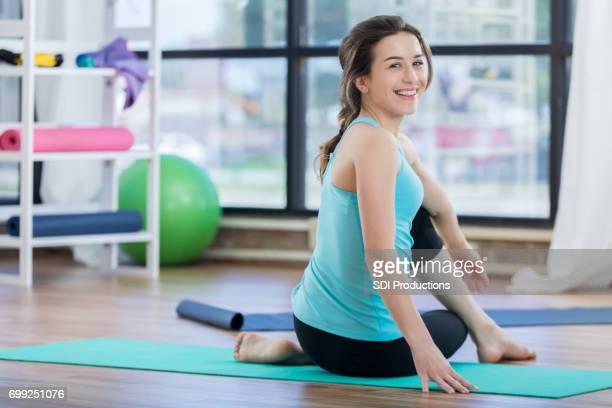 jeune femme s'étend sur sa jambe et le dos pendant les exercices au sol - gymnastique au sol photos et images de collection