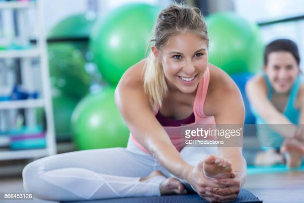 Young woman stretches her legs during yoga class