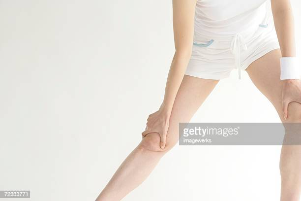 A young woman stretches her legs while exercising