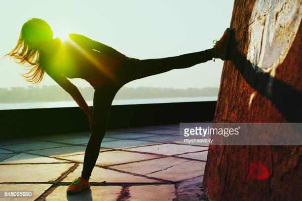 Young woman stretches near the river at dawn