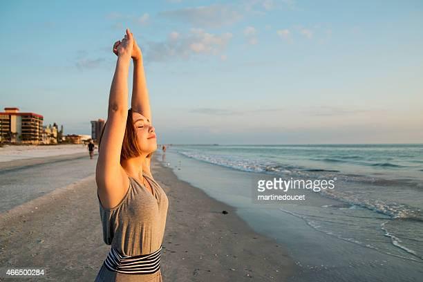 "young woman stretching and enjoying the sunset at the beach. - ""martine doucet"" or martinedoucet bildbanksfoton och bilder"