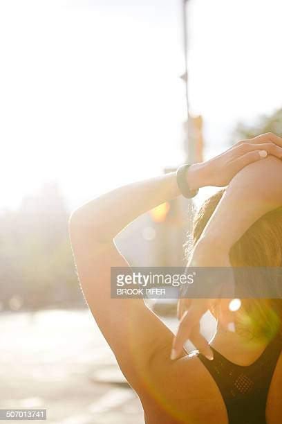 Young woman stretching arm in urban setting