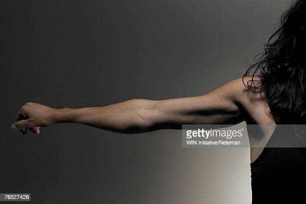 Young woman stretching arm