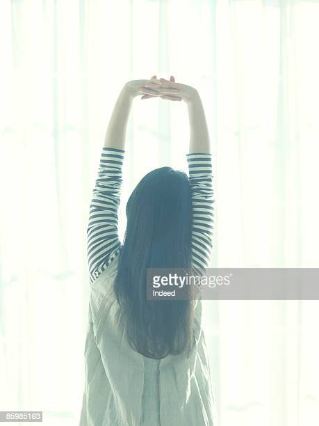 young woman stretching arms by window, rear view - tokyo motion ストックフォトと画像