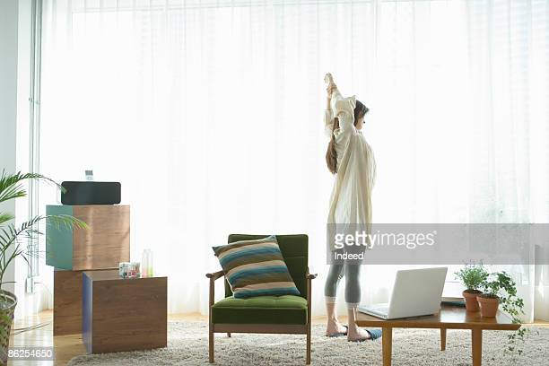 Young woman stretching arms in living room