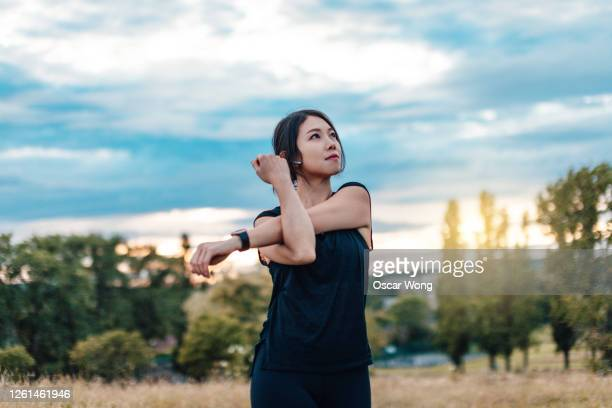 young woman stretching arms in the park after exercise - headphones stock pictures, royalty-free photos & images