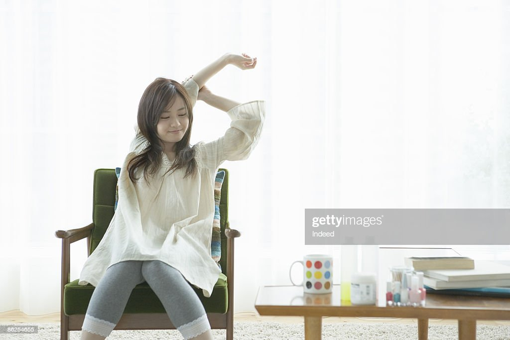 Young woman stretching arms on armchair : Stock Photo