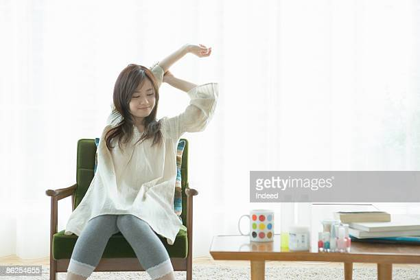 Young woman stretching arms on armchair