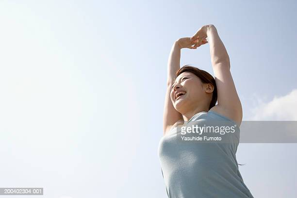 Young woman stretching arms outdoors, low angle view