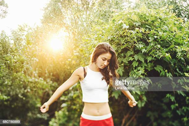Young woman stretching at sunset