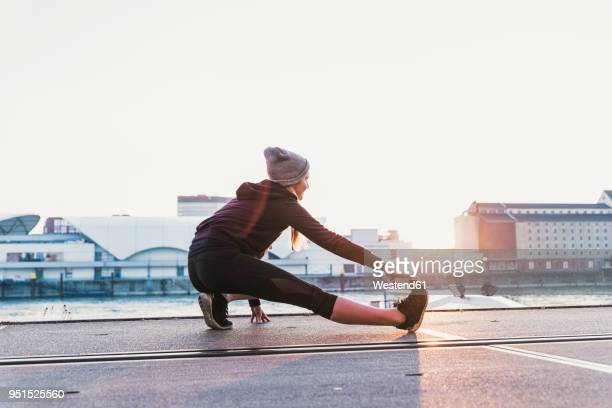young woman stretching at the riverside in the city at sunset - dehnen stock-fotos und bilder