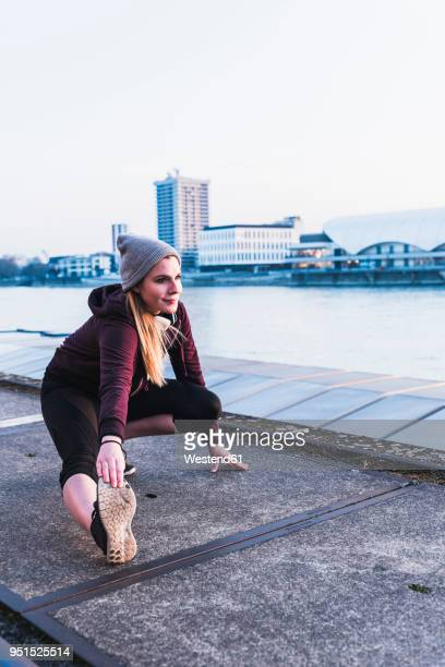 Young woman stretching at the riverside in the city