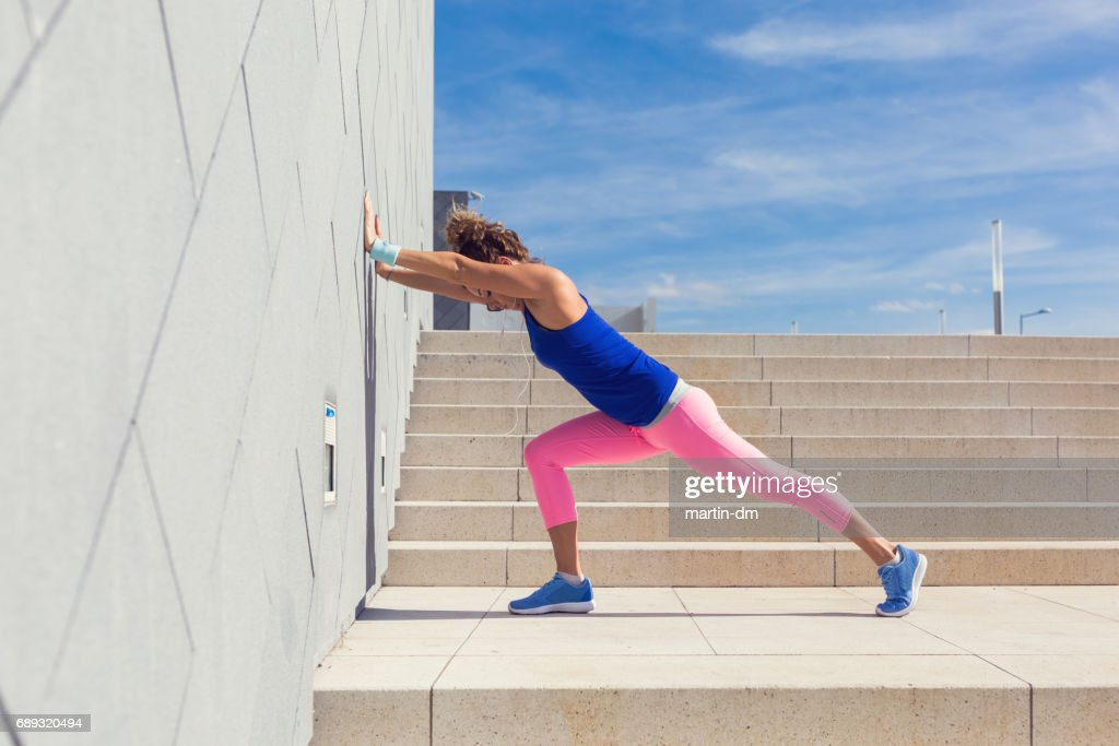 Young woman stretching before workout against surrounding wall : Stock Photo