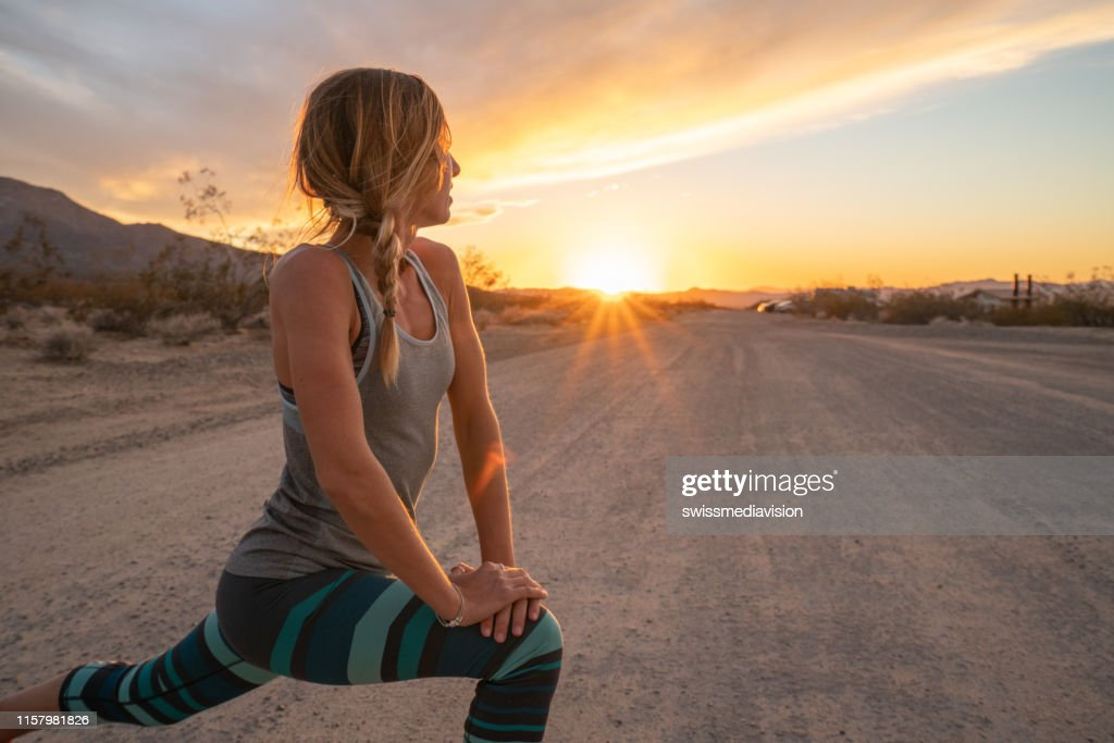 Young woman stretching body after jogging, sunset at the end of the road; female stretches body in nature : Stock Photo