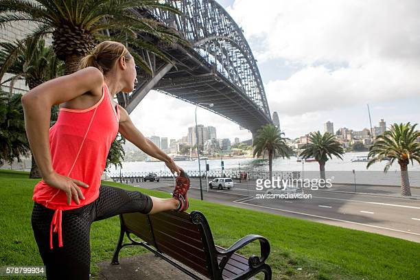 Young woman stretching by the Sydney harbour bridge