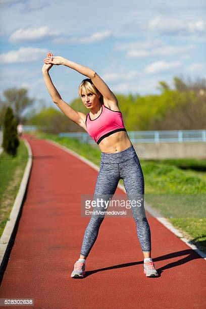 young woman stretching her arms after working out. - emir memedovski stock pictures, royalty-free photos & images