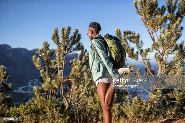 young woman stretching her leg on a hiking trip at the coast - frau beine breit stock-fotos und bilder