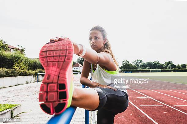 Young woman stretching in a track and field stadium