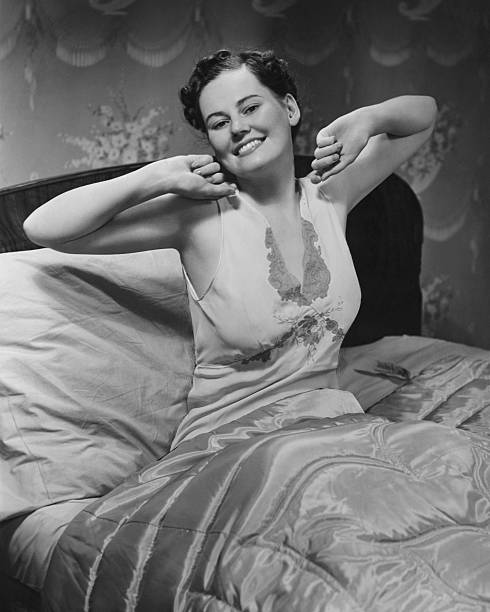 Young Woman Stretching In Bed, (B&W), Portrait Wall Art