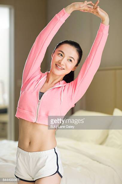 young woman stretching in bedroom - gymnastique douce photos et images de collection