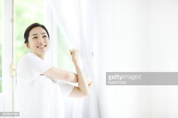 Young woman stretching in bedroom