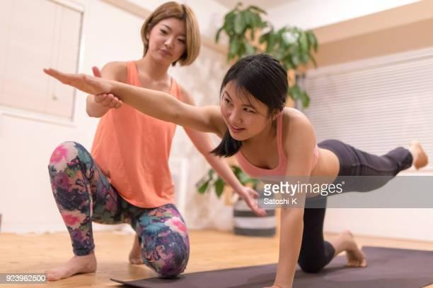 giovane donna che si allunga in classe di esercizio - solo adulti foto e immagini stock