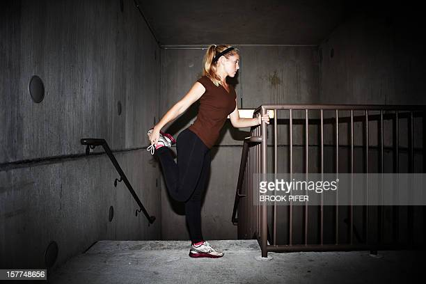 Young woman stretching in stairwell