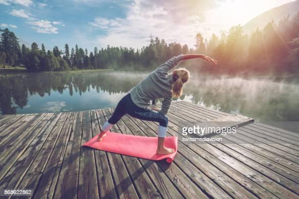 junge frau, die dehnung in der früh, yoga am see - körperbewusstsein stock-fotos und bilder