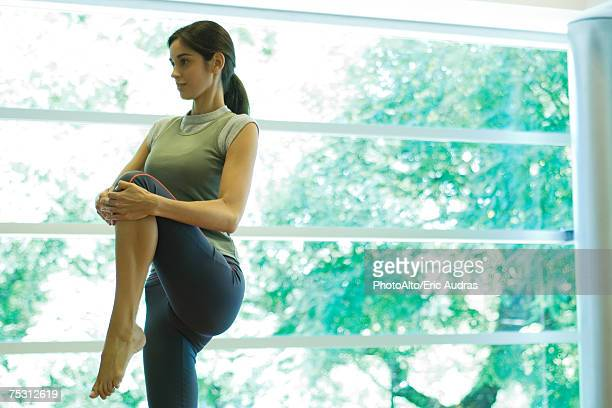 Young woman stretching knee